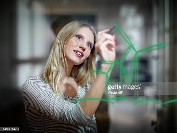 Germany, Cologne, Young woman drawing wind turbine on glass