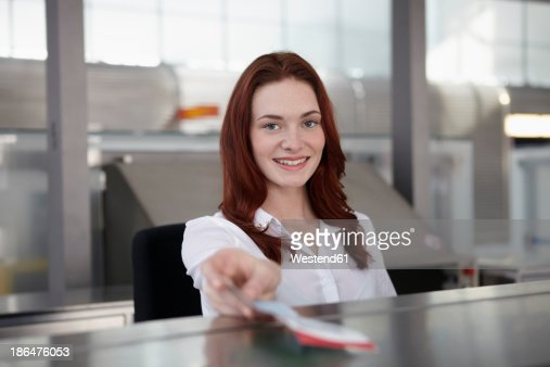 Germany, Cologne, Young woman giving ticket, smiling