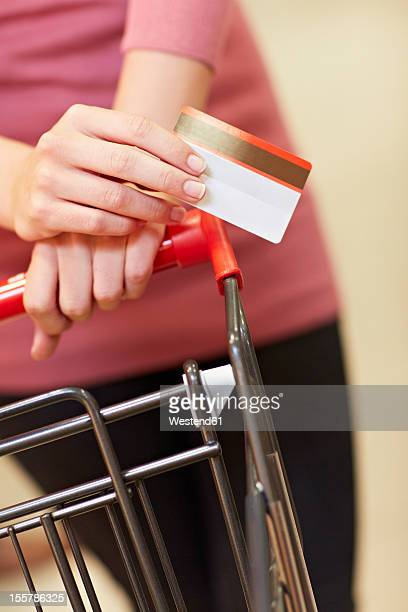 Germany, Cologne, Young woman holding credit card in supermarket
