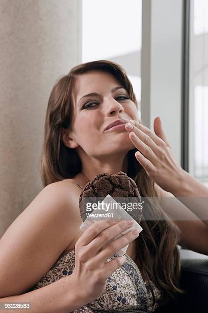 Germany, Cologne, Young woman holding piece of cake, portrait, close-up