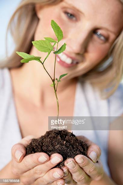 Germany, Cologne, Young woman holding seedling, smiling