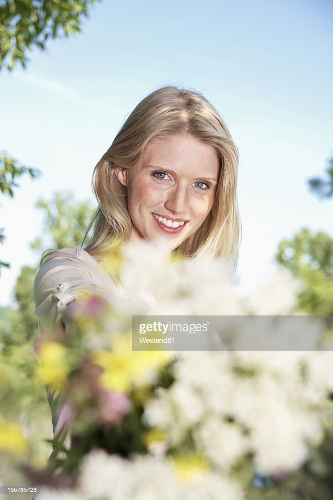 Germany, Cologne, Young woman holding wild flowers, smiling, portrait : Stock Photo