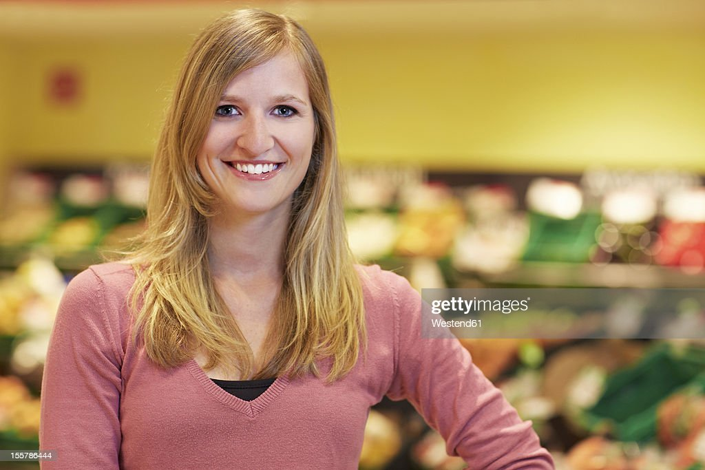 Germany, Cologne, Young woman in supermarket, smiling, portrait : Stock Photo