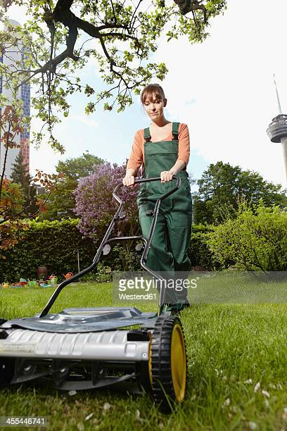 Germany, Cologne, Young woman mowing lawn with push mower