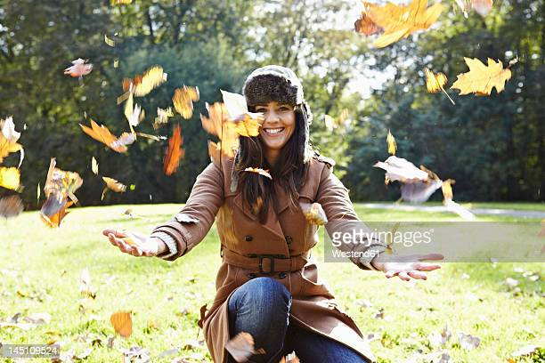 Germany, Cologne, Young woman playing in park with leaves, smiling, portrait