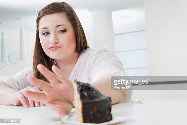 Germany, Cologne, Young woman refusing cake