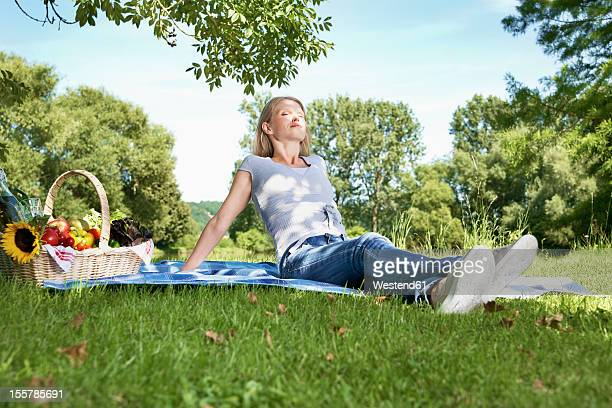 Germany, Cologne, Young woman relaxing at picnic