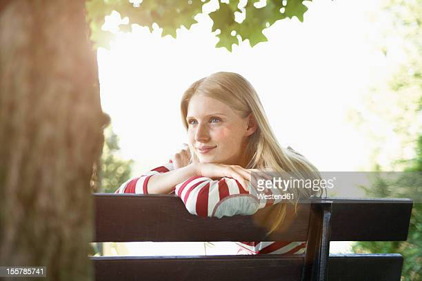 Germany, Cologne, Young woman sitting on park bench, smiling