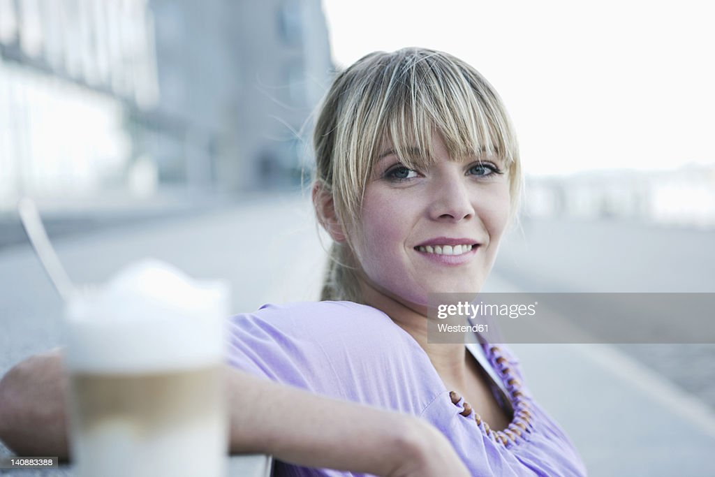 Germany, Cologne, Young woman smiling with coffee in foreground : Stock Photo