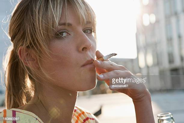 Germany, Cologne, Young woman smoking, portrait
