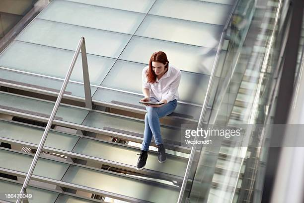 Germany, Cologne, Young woman using tablet
