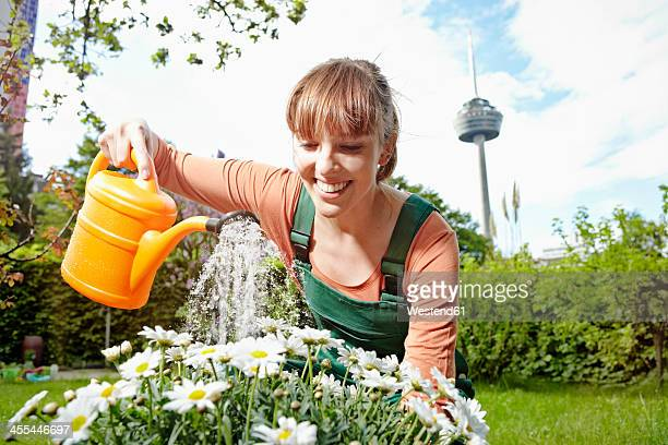Germany, Cologne, Young woman watering flowers, smiling
