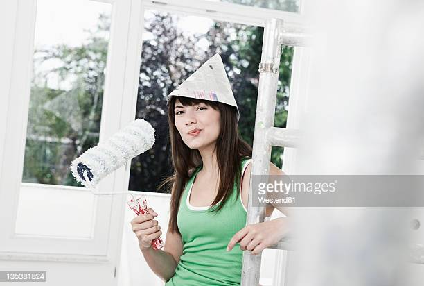 Germany, Cologne, Young woman wearing paper hat standing near scaffold in renovating apartment