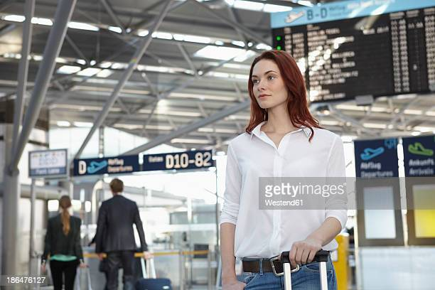 Germany, Cologne, Young woman with baggage at airport