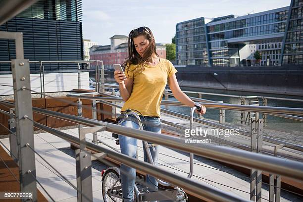 Germany, Cologne, young woman with bicycle looking at her smartphone