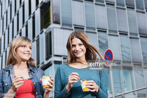 Germany, Cologne, Young woman with ice cream cup, smiling