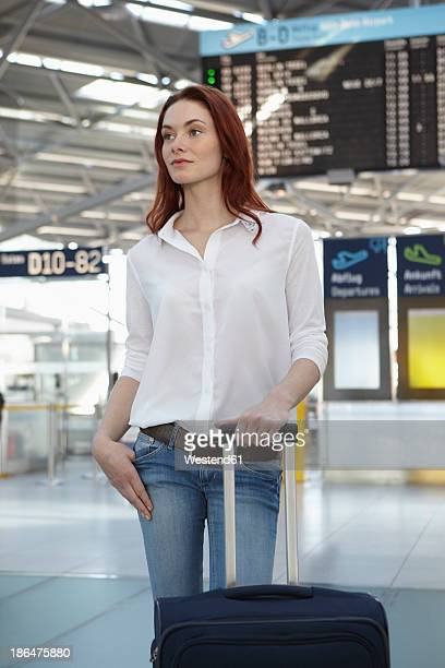 Germany, Cologne, Young woman with luggage at airport