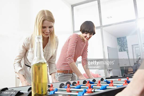 Germany, Cologne, Young women playing table soccer, smiling