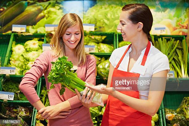 Germany, Cologne, Young womens with celery in supermarket