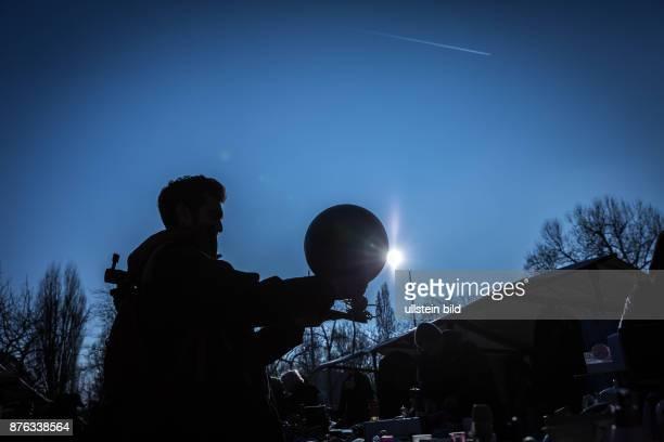 DEU Germany Deutschland Berlin Mann hält Globus am Stand eines Flohmarktes vor dem Rathaus Schöneberg igegen das Licht der Wintersonne