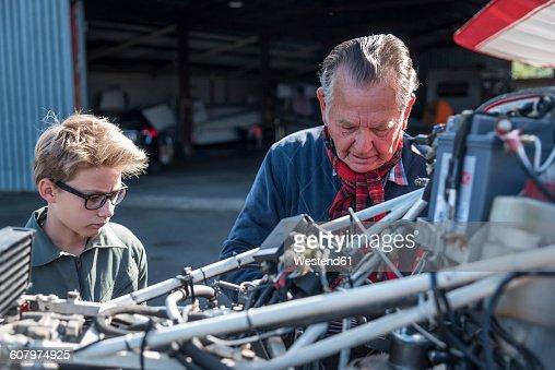 Germany, Dierdorf, Grandfather and grandson repairing biplane