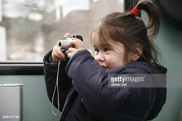 In a train A 4 years old girl is taking pictures of her mother and friends with a digital camera
