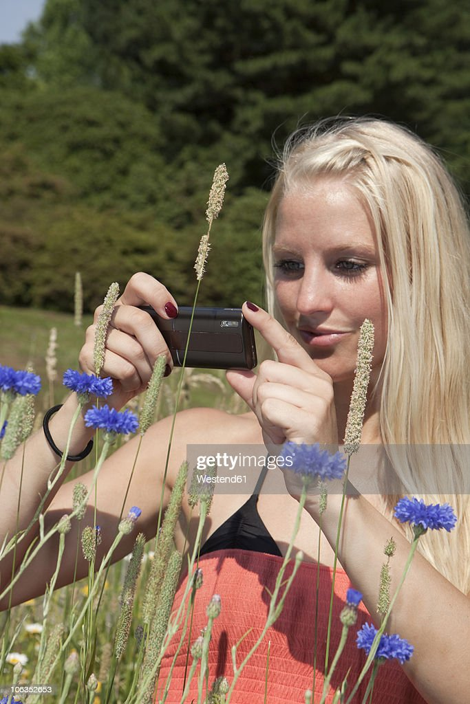 Germany, Dortmund, Young woman capturing an image with cell phone : Stock Photo