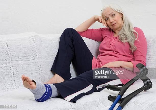 Germany, Düsseldorf, Woman with bandage sitting on sofa besides crutches