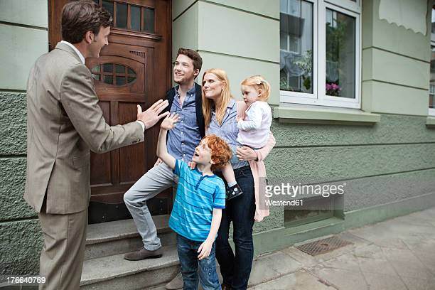 Germany, Duesseldorf, Boy giving high five to estate agent and family standing in background