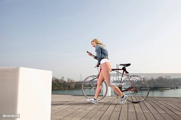 Germany, Duesseldorf, happy blond woman with bicycle and smartphone walking in front of Rhine River