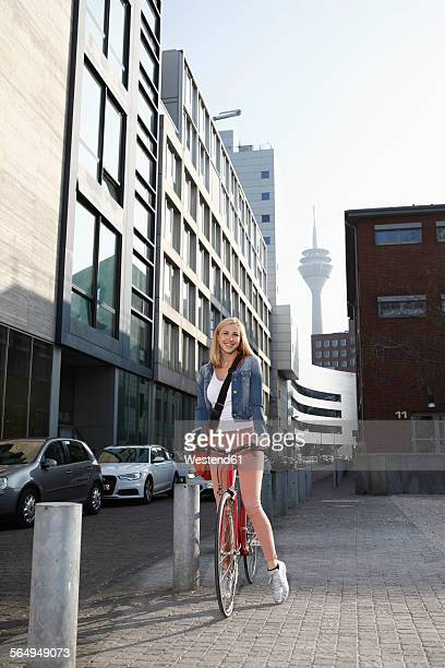 Germany, Duesseldorf, happy blond woman with bicycle