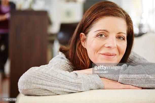 Germany, Duesseldorf, Mature woman relaxing on sofa, smiling