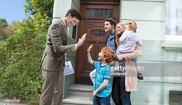 Germany, Duesseldorf, Real estate agent and family in front of house