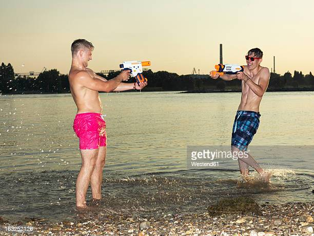 Germany, Duesseldorf, Young friends playing in water