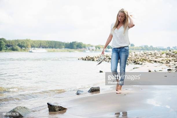Germany, Duesseldorf, young woman walking along riverside of Rhine