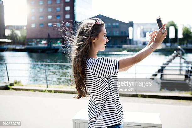 Germany, Duisburg, young woman taking a selfie with smartphone