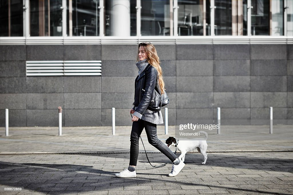 Germany, Dusseldorf, Young woman walking her dog