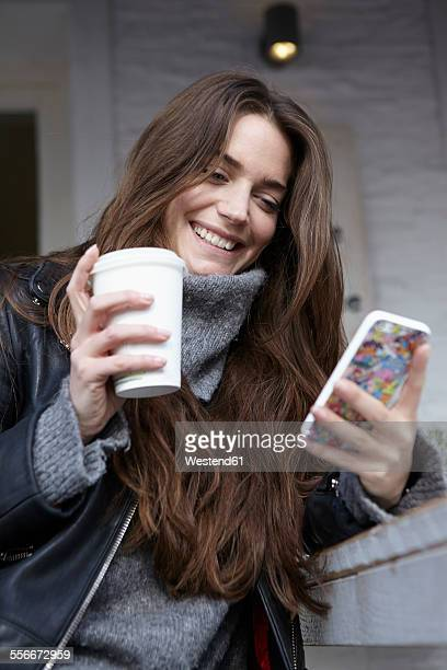 Germany, Dusseldorf, Young woman with coffee cup using smart phone