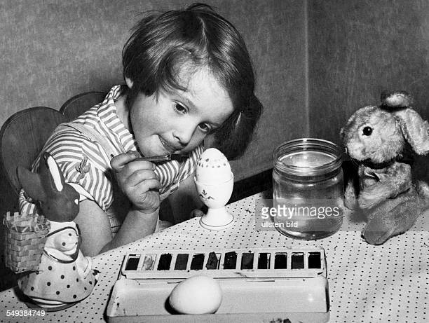 young girl painting easter eggs in the fifties