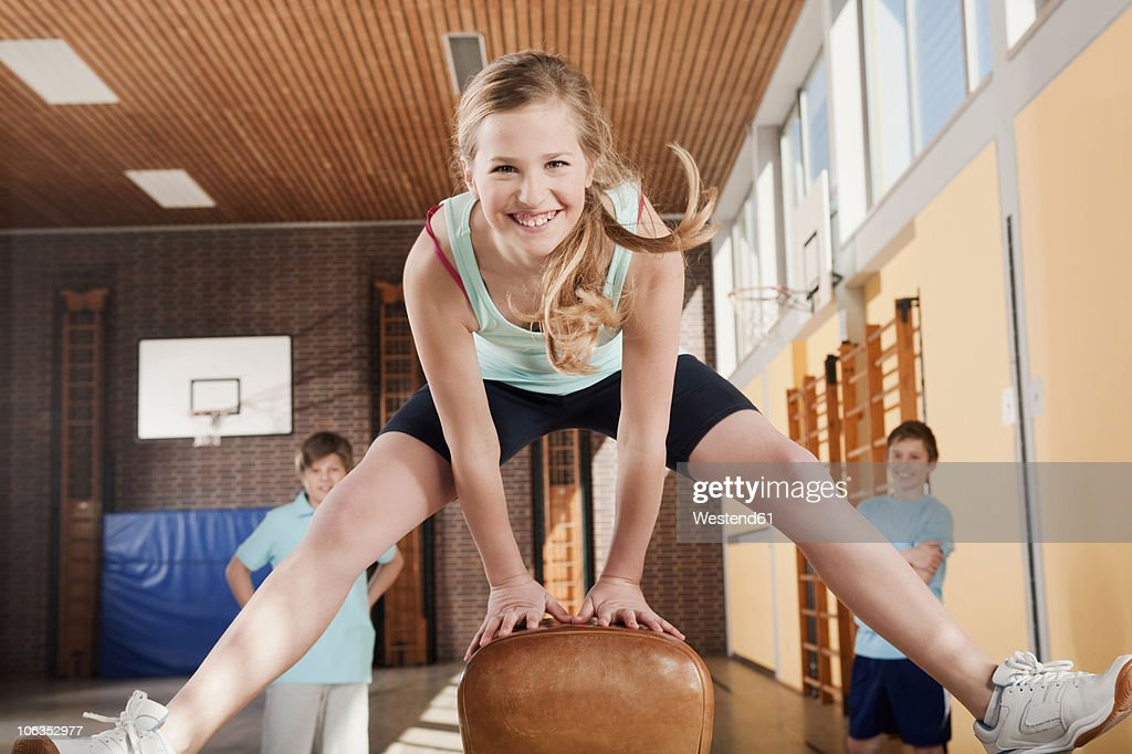 Germany, Emmering, Girl jumping with boys standing in background