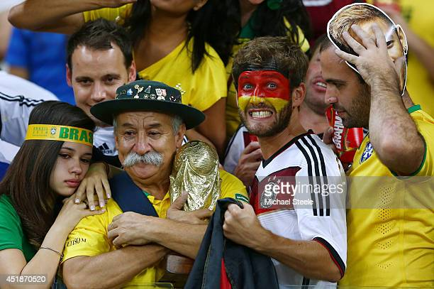 Germany fan reacts while surrounded by dejected Brazil fans after Germany's 71 win during the 2014 FIFA World Cup Brazil Semi Final match between...