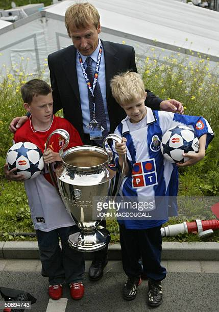 Football great Juergen Klinsmann of Germany poses two children wearing the Monaco and the Porto jersey and with the Champions' League trophy 25 May...