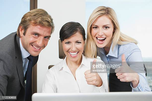 Germany, Frankfurt, Business people using laptop and showing thumbs up