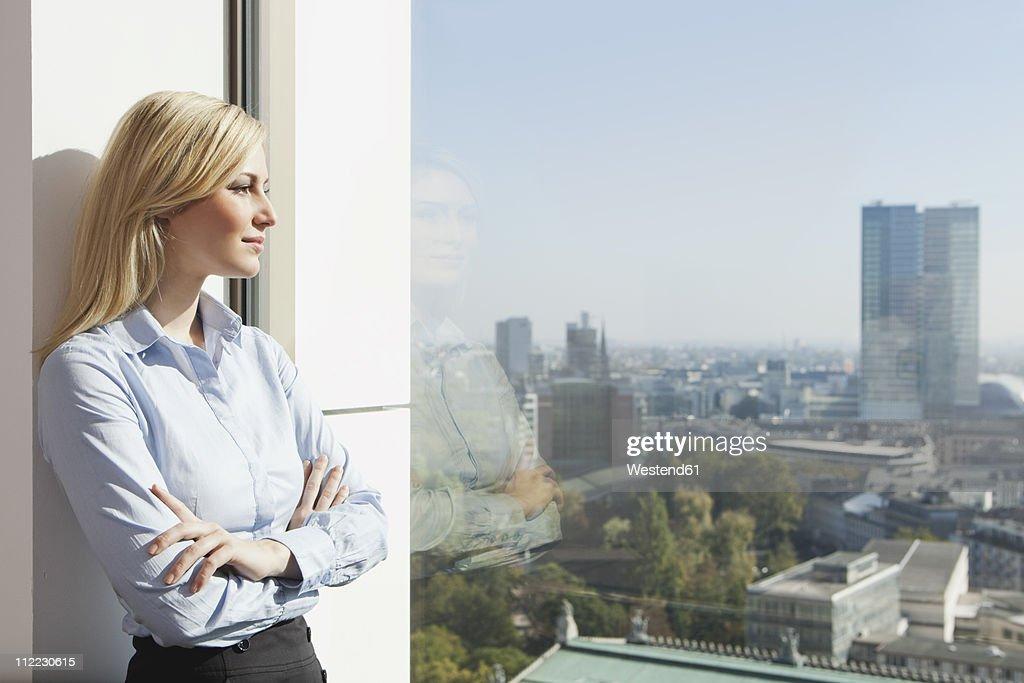 Germany, Frankfurt, Business woman looking through window