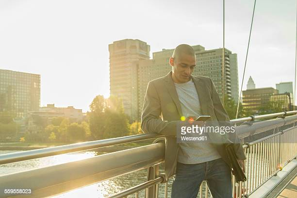 Germany, Frankfurt, businessman on bridge looking on smartphone