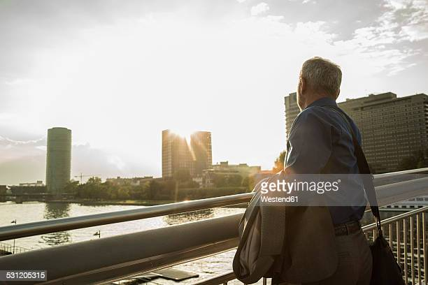 Germany, Frankfurt, businessman on bridge over river Main