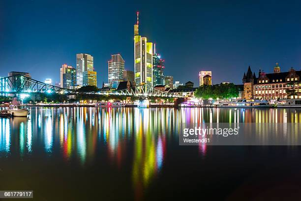 Germany, Frankfurt, lighted skyline with Main River in the foreground