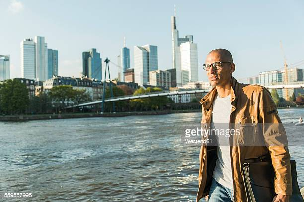 Germany, Frankfurt, man holding briefcase walking at the riverside