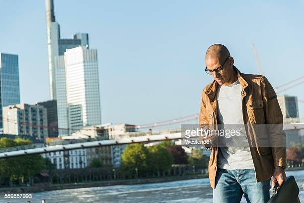 Germany, Frankfurt, man looking on smartphone