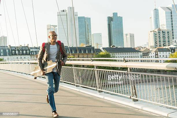 Germany, Frankfurt, man running with skateboard on bridge
